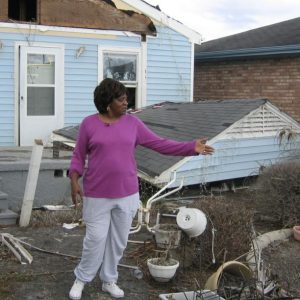 Woman shows a destroyed home