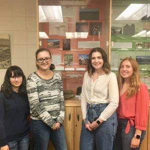 Anthropology and Geography students (left to right) Morgan Wilson, Jessie McCaig, Karlie Dorland, and Kit Kelly in front of the exhibition they designed in ANTH 462