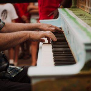 Man playing 100th anniversary piano
