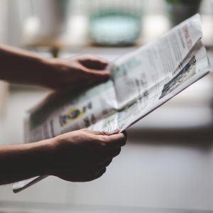 person holding newspaper reading