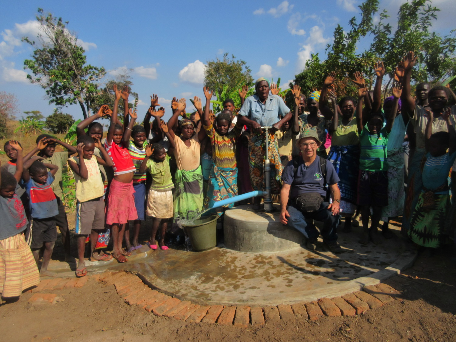 Group of villagers and Jim stand for photo in front of new shallow well