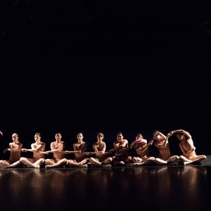 Ten female dance students - 9 are sitting and one is standing during a performance