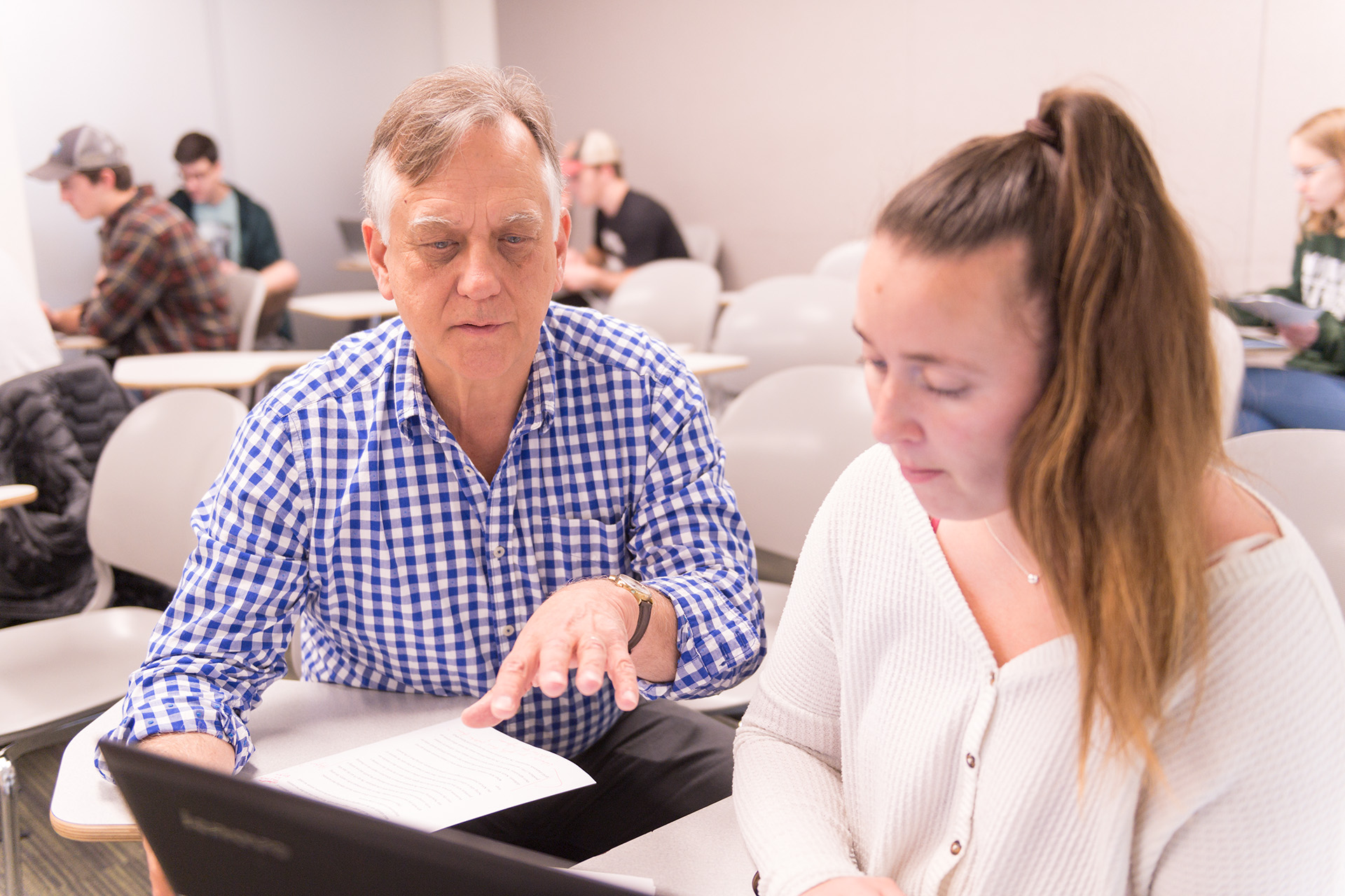 Colorado State University Economics professor Ed Barbier talks with a student in a capstone class about her project, May 2, 2019.