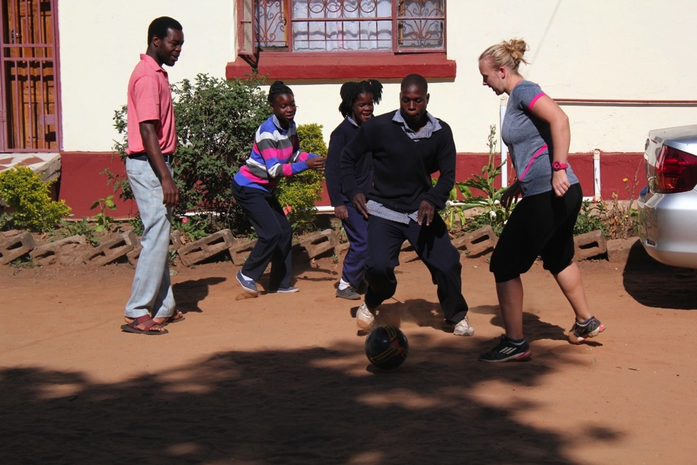 Student Andrew shows off his amazing football skills to fellow volunteer Fiona during sports