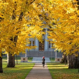 Student walks through oval in Fall