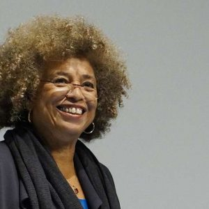 Angela Davis smiling in front of a gray background