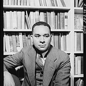 Richard Wright in black and white, wearing a three piece suit and sitting in front of a bookcase