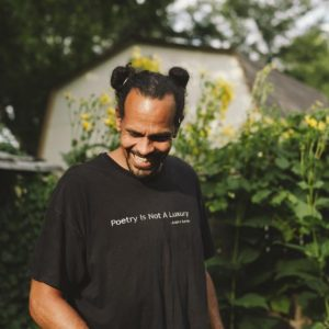 Ross Gay in a garden, looking down and smiling