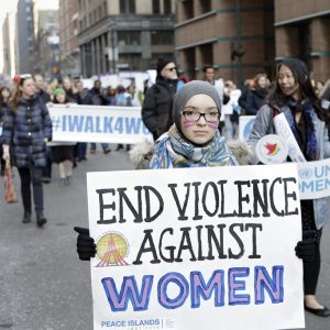 Image from International Women's Day, woman holding sign.