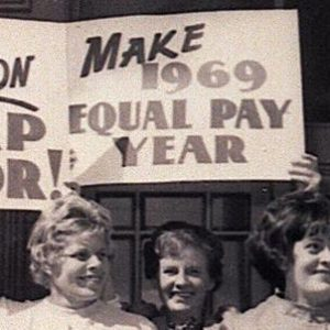 Women holding signs about equal work equal pay at one of the first Equal Pay Day rallies