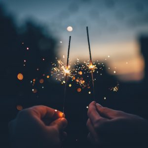 Two hands, each holding a sparkler.