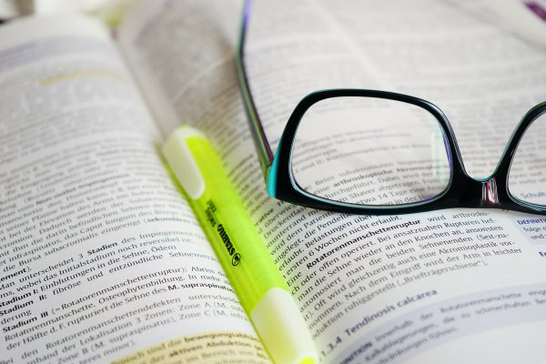 Glasses and highlighter resting on book