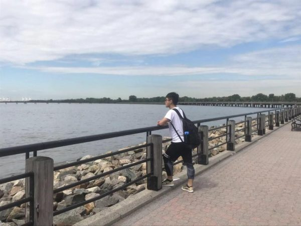 Leon Chen standing next to a body of water