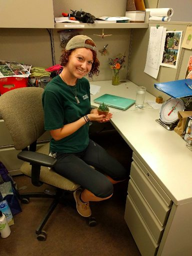 Kenna Castleberry sitting at a desk holding a plant