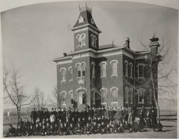 A group of young men and women stand, kneel, sit, or lounge in front Old Main in 1886.