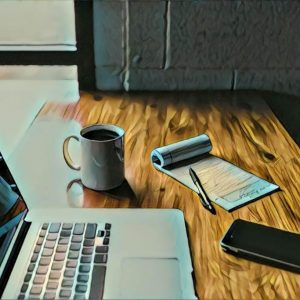 desk with laptop, notepad, phone, and cup of coffee