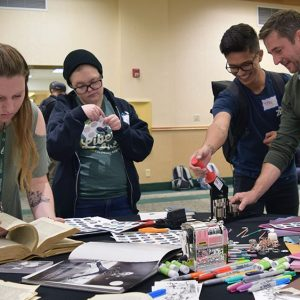 a group of students standing around a table with craft supplies at the 2019 possibilities fair