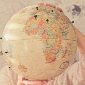 Globe with thumbtacks marking locations