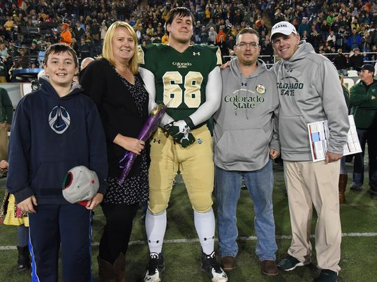 CSU defensive lineman Justin Hansen (68) is joined by, from left, his younger brother Logan, mother Kara, father Thomas and coach Mike Bobo at Hughes Stadium on Senior Night. (Photo: Don Reichert/CSU Athletics)