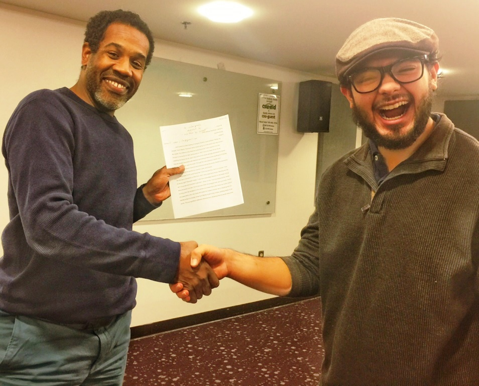 Cesar Ita gives Gregory Pardlo a copy of his midterm, an analysis of Pardlo's Pulitzer Prize-winning book of poetry, Digest