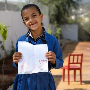 Young girl from Jerash refugee camp holds a self portrait drawn in crayon