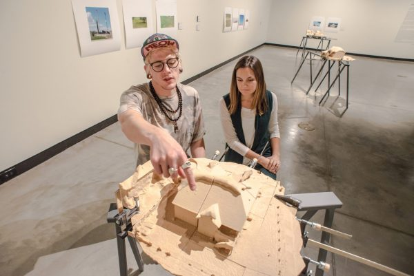 Kyle Singer and Emily Sullivan point to a detail on one of David Brooks' fracking-inspired art pieces