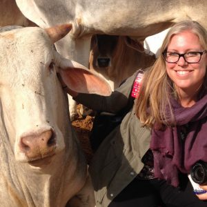Kelsi Nagy smiles with cows in India during research trip