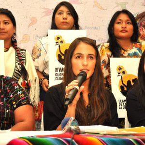 Juliana Velez speaking at a summit in Geatemala, surrounding by other leaders fighting for women's rights