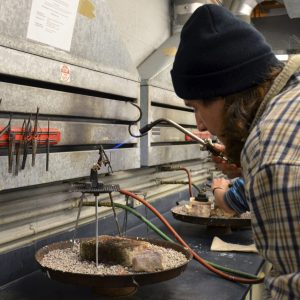 Student using a blow torch in a metalsmithing class