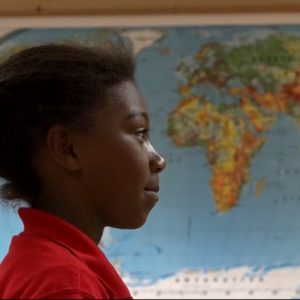 School-aged girl standing in a classroom in front of a world map