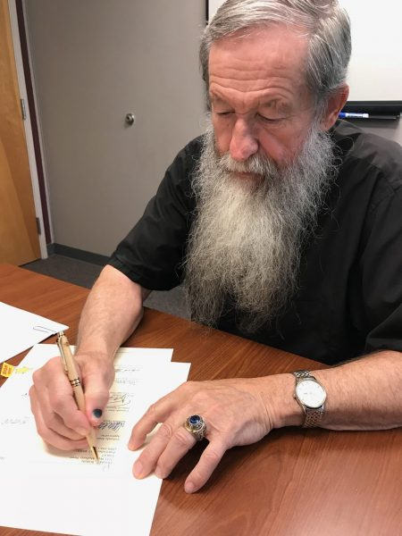 Don Williette signing donation letter