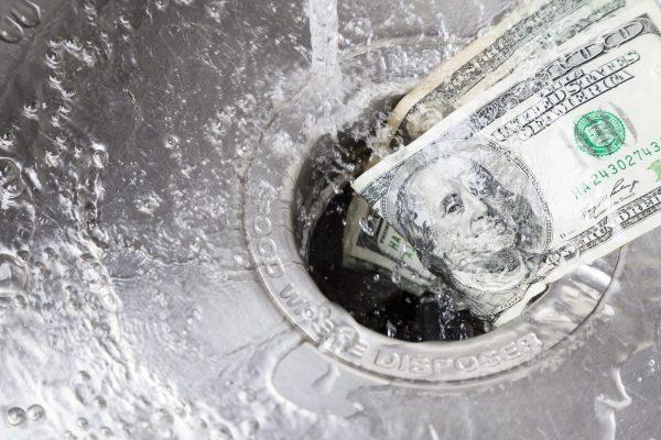 Cash being flushed down a kitchen sink drain