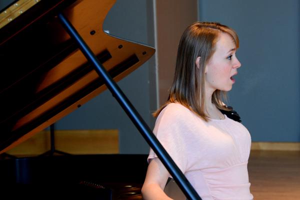 Vanessa Doss sings at a piano