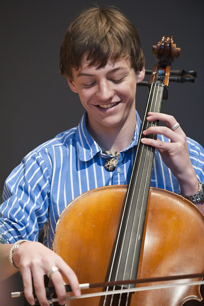 A high school student plays the cello