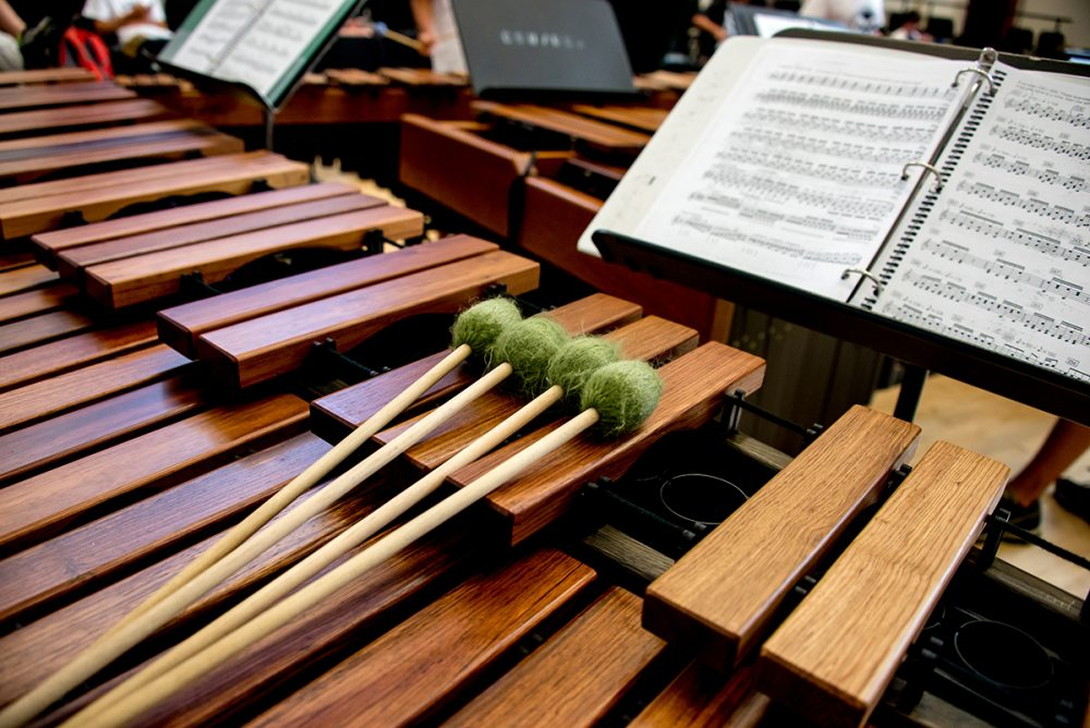 A marimba with four mallets is pictured next to sheet music