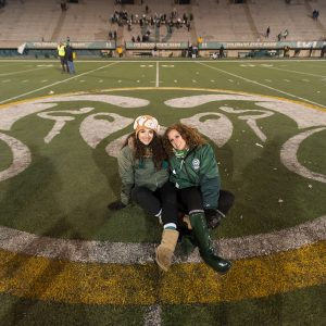 Jennifer Clary and her daughter sit in the middle of the field at Hughes Stadium