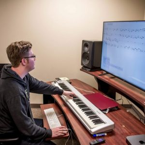 """Music composition major, Derek Summers, works in Finale on the first movement his original composition, a violin, clarinet, and piano trio called """"Arcs."""""""