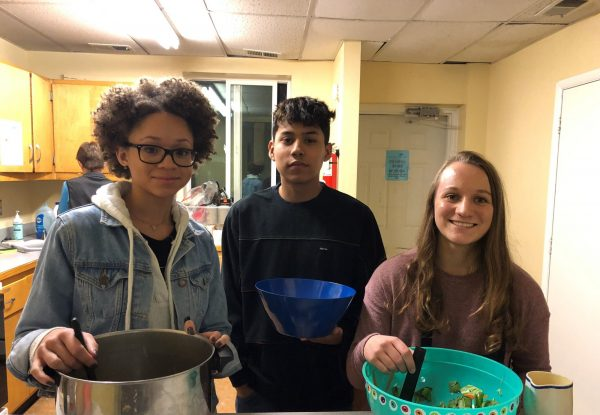 Philosophy students pose for photo while cooking