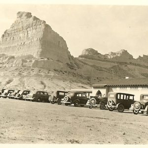 A line of antique cars line up in front of a building, rock formations loom above them.
