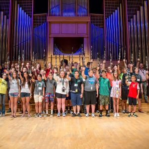 Several dozen middle and high school clarinet students pose for a group photo in the Organ Recital Hall