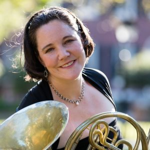 Jennifer Montone headshot - pictured with a French Horn