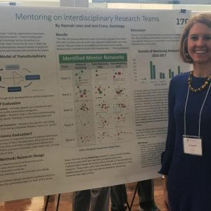 Graduate student stands with her research poster project