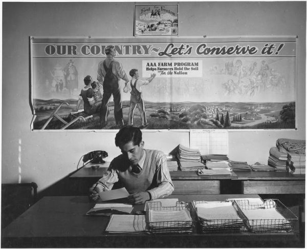 An Agricultural Adjustment Administration representative in his office, Taos County, New Mexico, December 1941. The agency was created under the New Deal to reduce farm surpluses and manage production.