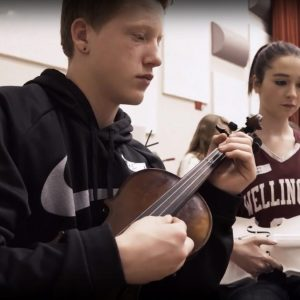 A high school student assists a middle school student on the violin