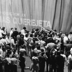 Black and white image of crowd behind curtain