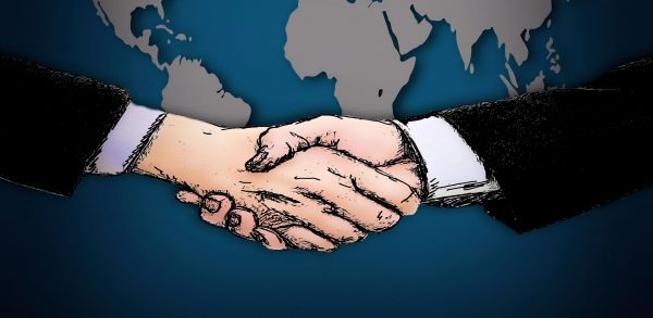 Two hands shake over a map of the world