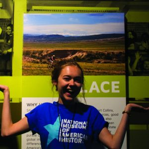 Heidi Fuhrman posting in front of museum exhibit about innovation in Fort Collins