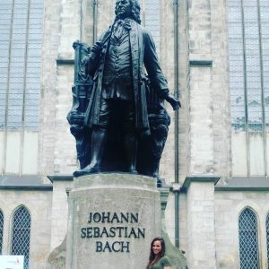 Angela Lamar posing next to statue of Johann Sebastian Bach