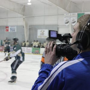 Student uses professional film equipment to report on hockey game