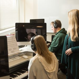 Instructor with students in the keyboard composition lab